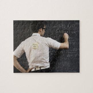 Nerdy man writing on blackboard jigsaw puzzle