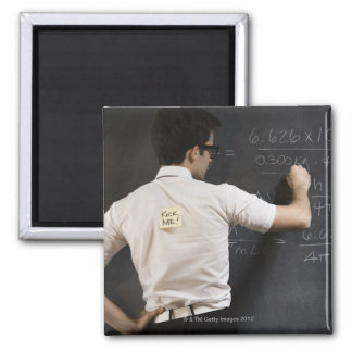 Nerdy man writing on blackboard magnet