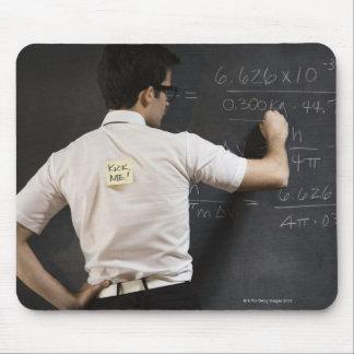 Nerdy man writing on blackboard mousepads