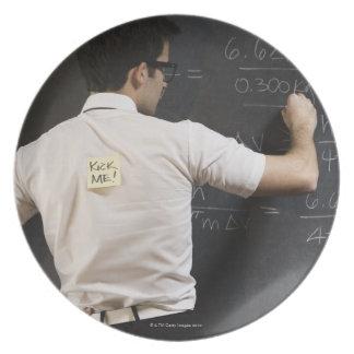 Nerdy man writing on blackboard party plate