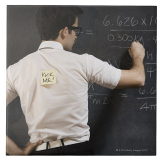Nerdy man writing on blackboard tile