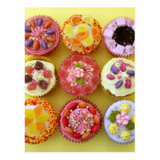 Nine cupcakes each decorated with candy in a post cards