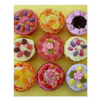 Nine cupcakes each decorated with candy in a print