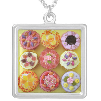 Nine cupcakes each decorated with candy in a silver plated necklace
