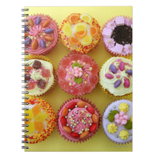 Nine cupcakes each decorated with candy in a spiral notebook