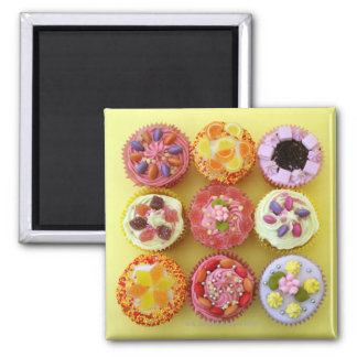 Nine cupcakes each decorated with candy in a square magnet