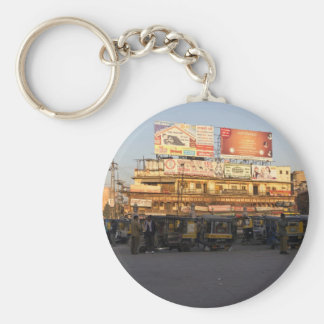 Number of parked auto rickshaws, shops and people basic round button key ring
