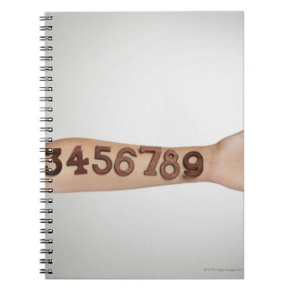 numbers affixed to the arm,ands close-up notebook