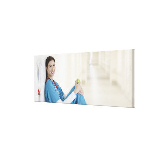 Nurse sitting with apple in hospital corridor stretched canvas prints