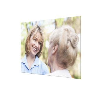 Nurse smiling and talking to a senior woman canvas print