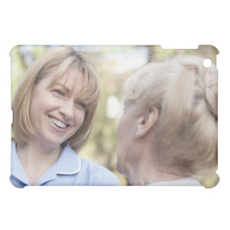 Nurse smiling and talking to a senior woman iPad mini covers