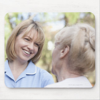 Nurse smiling and talking to a senior woman mouse pad