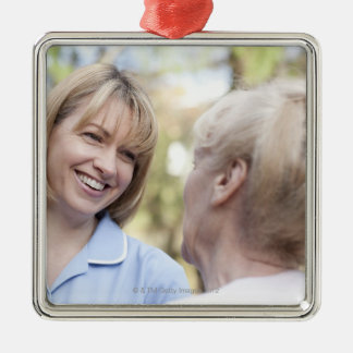 Nurse smiling and talking to a senior woman Silver-Colored square decoration