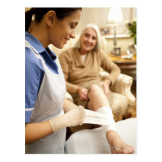 Nurse wrapping bandage on senior woman's leg to postcard
