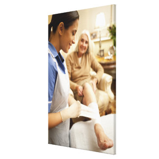 Nurse wrapping bandage on senior woman's leg to stretched canvas print