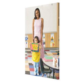 Nursery teacher by girl (3-5) with painting, canvas print
