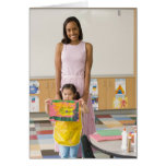Nursery teacher by girl (3-5) with painting, cards