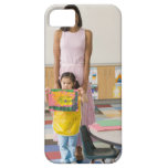 Nursery teacher by girl (3-5) with painting, iPhone 5 covers