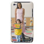 Nursery teacher by girl (3-5) with painting, iPod touch covers