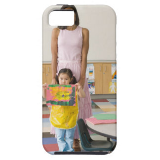 Nursery teacher by girl (3-5) with painting, case for the iPhone 5