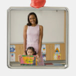 Nursery teacher by girl (3-5) with painting, christmas tree ornaments