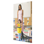 Nursery teacher by girl (3-5) with painting, gallery wrapped canvas