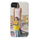 Nursery teacher by girl (3-5) with painting, iPhone 4 case