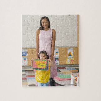Nursery teacher by girl (3-5) with painting, jigsaw puzzle