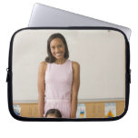 Nursery teacher by girl (3-5) with painting, laptop sleeve