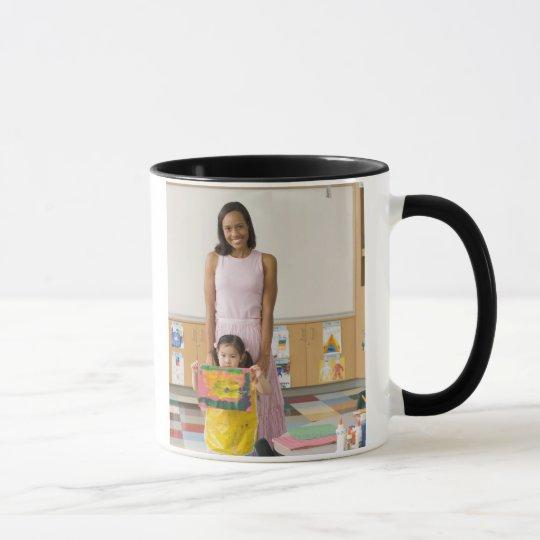 Nursery teacher by girl (3-5) with painting, mug