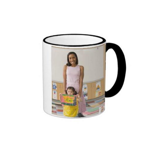 Nursery teacher by girl (3-5) with painting, coffee mug