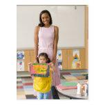 Nursery teacher by girl (3-5) with painting, postcard