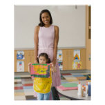 Nursery teacher by girl (3-5) with painting, poster