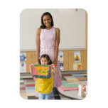 Nursery teacher by girl (3-5) with painting, flexible magnet