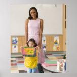Nursery teacher by girl (3-5) with painting, print