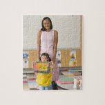 Nursery teacher by girl (3-5) with painting, puzzles