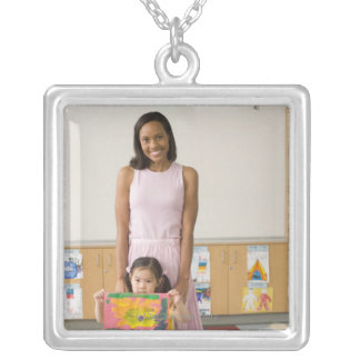 Nursery teacher by girl (3-5) with painting, square pendant necklace