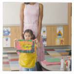 Nursery teacher by girl (3-5) with painting, large square tile