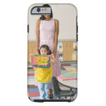 Nursery teacher by girl (3-5) with painting, tough iPhone 6 case
