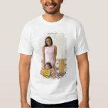 Nursery teacher by girl (3-5) with painting, tshirt