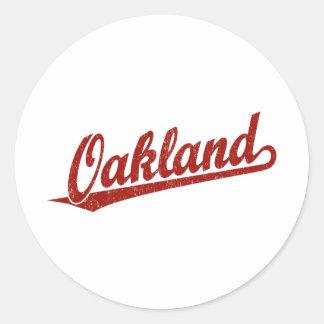 Oakland script logo in red distressed round sticker