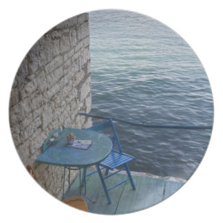 Oceanside seating for two at tiny outdoor cafe, plate