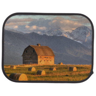 Old barn framed by hay bales and dramatic car mat