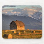 Old barn framed by hay bales and dramatic mousepad