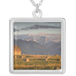 Old barn framed by hay bales and dramatic silver plated necklace