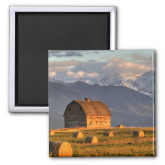 Old barn framed by hay bales and dramatic square magnet