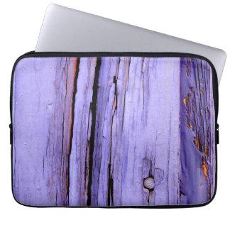 Old cracked purple paint on wood laptop sleeve