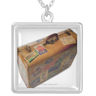 old fashioned suitcase with travel stickers silver plated necklace