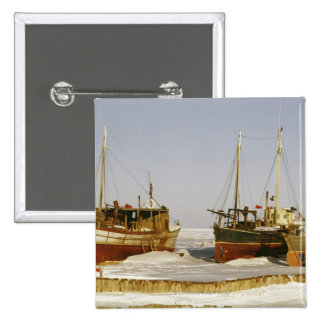 Old-fashioned, weathered fishing boats beached pinback button