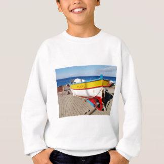 Old fishing boat drawn up on pavement. sweatshirt